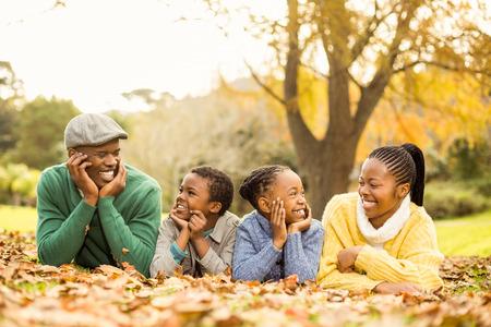 Porträt einer lächelnden jungen Familie in den Blättern auf einem Herbste Tag liegend