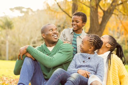 hombres negros: Portrait of a young family sitting in leaves on an autumns day