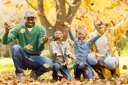 Young smiling family throwing leaves around on an autumns day Archivio Fotografico