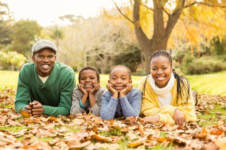 jovenes felices: Retrato de una familia sonriente joven que miente en hojas en un día otoños Foto de archivo