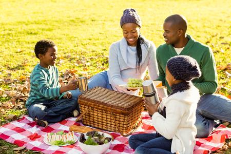 Jeune famille souriante faire un pique-nique sur une journée des automnes