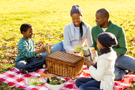 green and black: Young smiling family doing a picnic on an autumns day