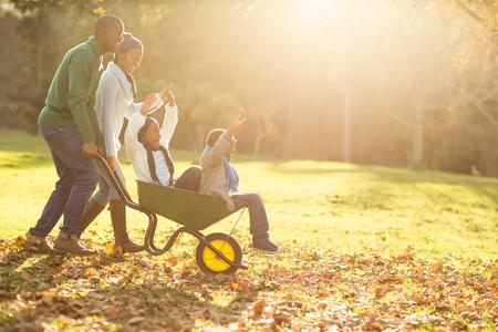 carretilla: Los padres jóvenes que sostienen a sus hijos en una carretilla en un día otoños Foto de archivo