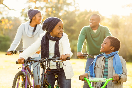 green and black: Young smiling family doing a bike ride on an autumns day