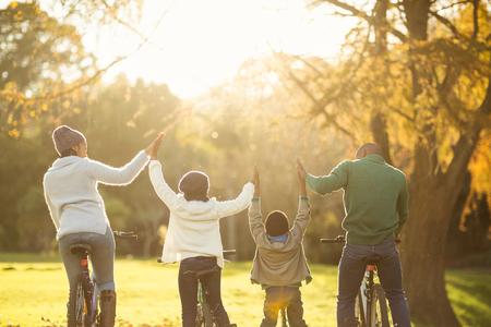 black girl: Rückansicht einer jungen Familie mit den Armen auf dem Fahrrad auf einem Herbst Tag auferweckt