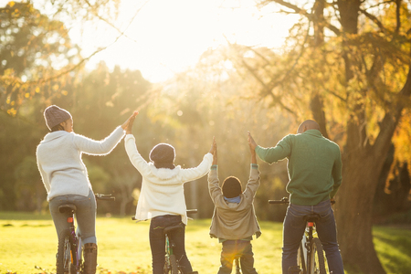 Rear view of a young family with arms raised on bike on an autumns day Banque d'images