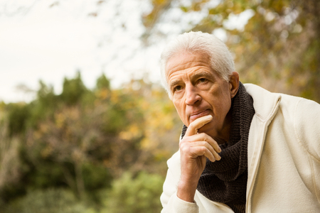 apprehensive: Senior man in the park on an autumns day