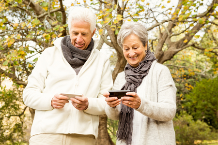 mobile sms: Senior couple in the park on an autumns day