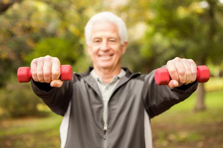 fuerza: Hombre mayor que trabaja en el parque en un día otoños