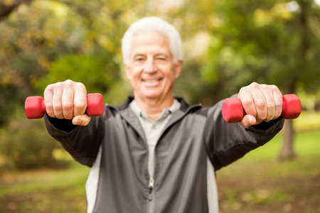 man working out: Senior man working out in park on an autumns day