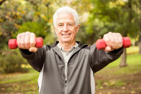 tercera edad: Hombre mayor que trabaja en el parque en un día otoños
