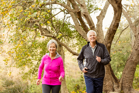 Exercising: Senior couple in the park on an autumns day