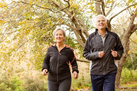 ancianos caminando: Matrimonios de edad en el parque en un día otoños