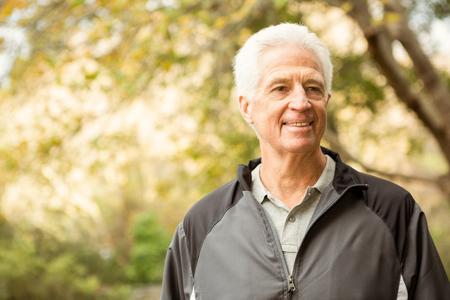 Älterer Mann im Park an einem Tag Herbste