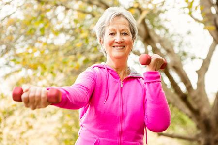 levantando pesas: Superior de la mujer en el parque en un día otoños