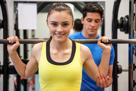 trainers: Woman lifting barbell with trainer spotting her at the gym Stock Photo