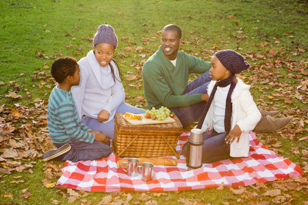 picnicking: Happy family picnicking in the park together  on an autumns day Stock Photo