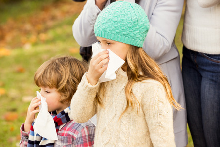 sick day: Sick family blowing their noses on an autumns day
