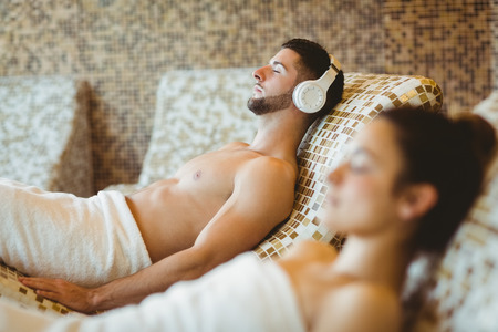 woman listening to music: Man and woman lying down together at the spa