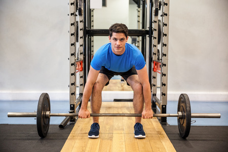 barbell: Focused man about to lift a barbell at the gym Stock Photo