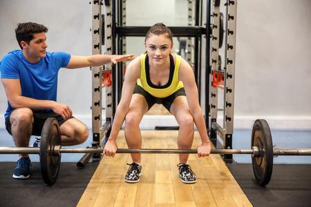 Femme de levage barbell et poids avec formateur regarder au gymnase