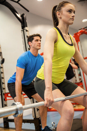 fitness training: Man and woman lifting barbells together at the gym Stock Photo