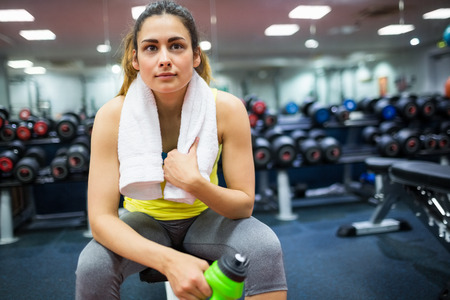 workouts: Woman resting in between workouts at the gym Stock Photo