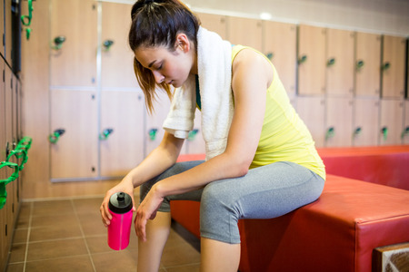 locker room: Tired woman after a workout in the gym locker room Stock Photo