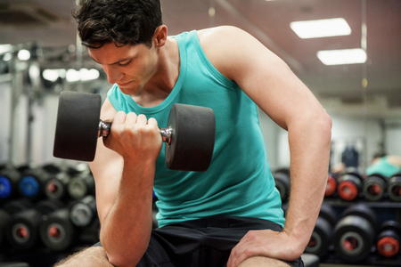gym: Man lifting dumbbell weight while sitting at the gym