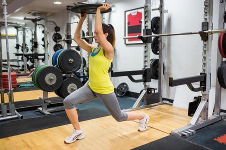 lunges: Mujer decidida que hace estocadas mientras sostiene una sobrecarga de peso en el gimnasio
