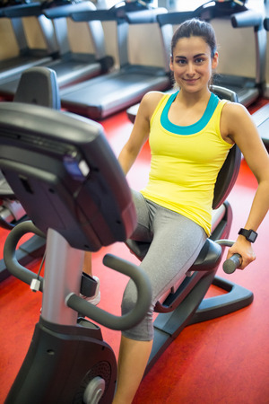 exercise machine: Smiling woman using exercise machine at the gym