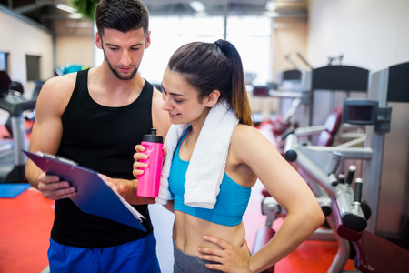 regime: Trainer explaining workout regime to woman at the gym