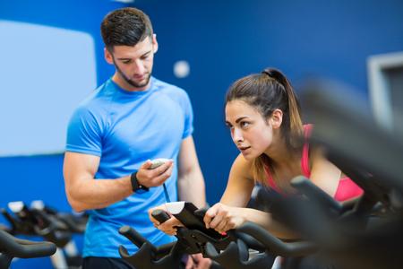 gimnasio: Mujer en bicicleta de ejercicio con entrenador de su sincronización en el gimnasio Foto de archivo