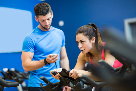 stopwatch: Woman on exercise bike with trainer timing her at the gym Stock Photo