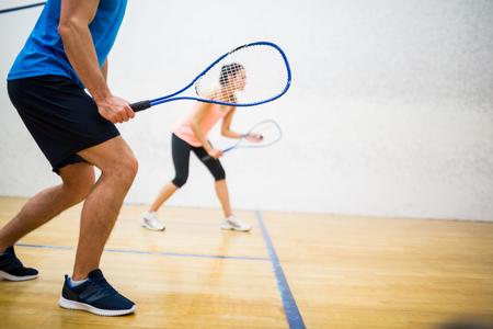 Frau über den Ball im Squash-Court zu dienen