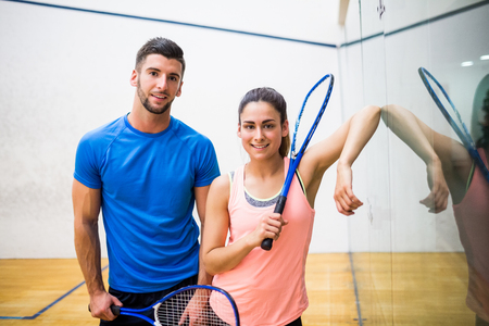 squash: Happy couple about to play squash in the squash court Stock Photo