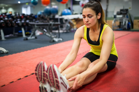 young woman legs up: Woman doing warm up exercises at the gym