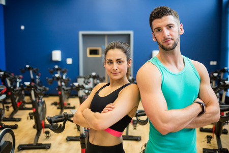 working out: Focused couple working out together at the gym