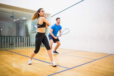 Couple play some squash together in the squash court Stock Photo - 47305827