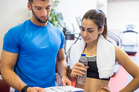 personal trainer woman: Trainer and athlete discussing workout plan at the gym