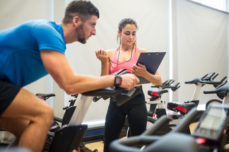 Trainer timing man on exercise bike at the gym