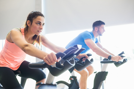 Man and woman using cycling exercise bikes at the gym