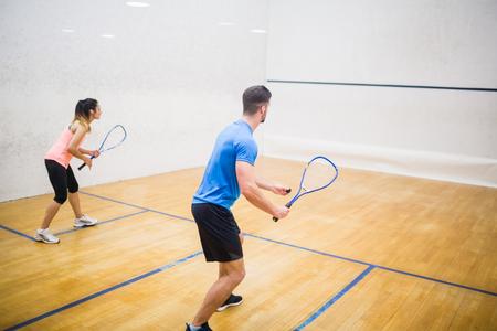 Paar genieten van een partijtje squash in de squashbaan Stockfoto