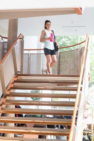 down the stairs: Mujer caminando por las escaleras en el gimnasio Foto de archivo