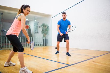 Couple jouer de la courge ensemble dans la cour de squash