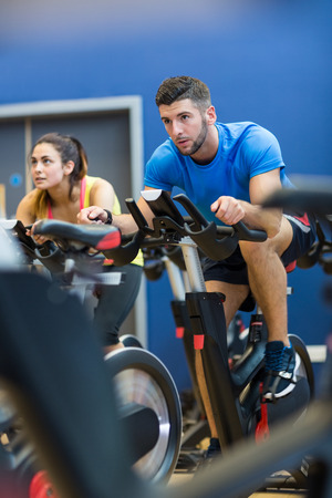 caucasian man: Focused couple using exercise bikes at the gym Stock Photo