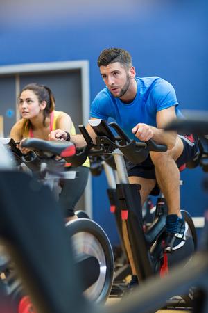 Pareja enfocada utilizando bicicletas de ejercicio en el gimnasio Foto de archivo - 47305953