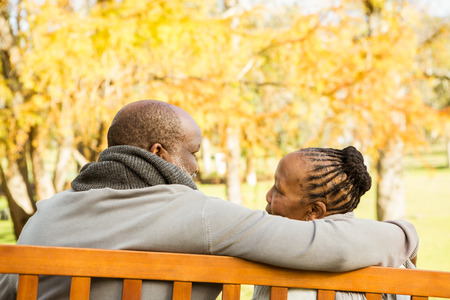 together: Happy senior couple discussing together on a bench in parkland