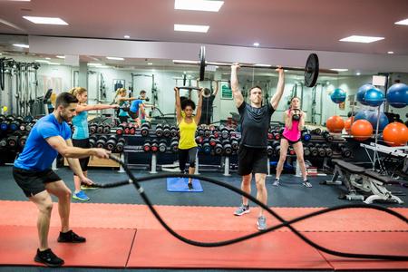 adentro y afuera: Las personas en forma de trabajo a cabo en la sala de pesas en el gimnasio