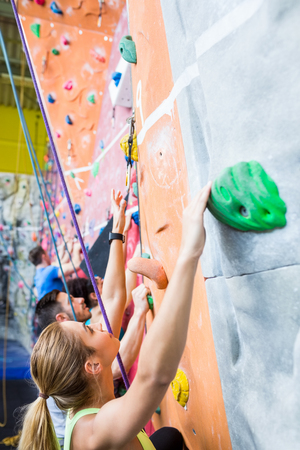 recreational climbing: Fit people rock climbing indoors at the gym
